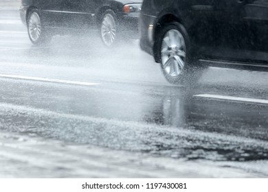 cars moving in high speed on flooded city road spraying water from the wheels