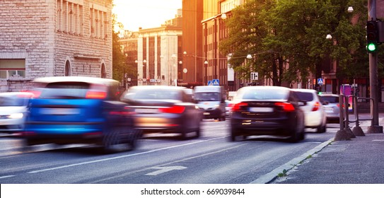 Cars moving on the urban road at dusk in summer. Transport in the city