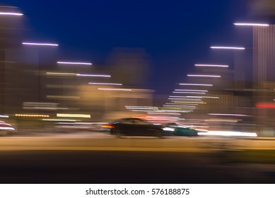 Cars moving at speed through a junction with significant motion blue providing streaks of light against a dark sky.