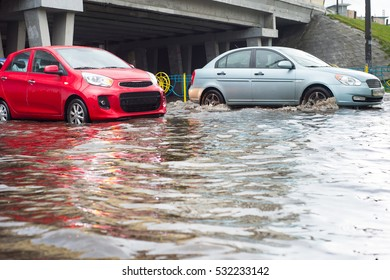 Cars on a flooded city road during the rain