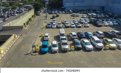 Cars on an outdoor parking lot in department store. All trademark removed.