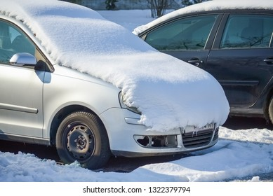 Cars on a parking lot covered with snow in a cold winter day