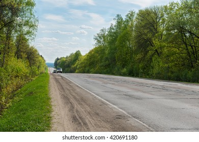 cars on the road in a wooded area