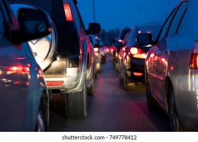Cars on urban street in traffic jam at twilight