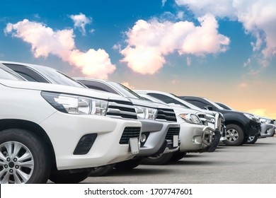 Cars park in asphalt parking lot in a row with cloudy sky background in nature. Outdoor parking lot with fresh ozone, green environment of transportation and technology concept