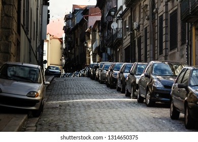 Cars parked along the pavement streets of the old town.