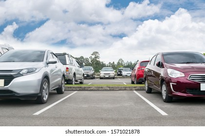 Cars parked in asphalt parking lot. Trees, white cloud blue sky background, empty space for car parking. Outdoor parking lot with green environment. nature travel transportation technology concept