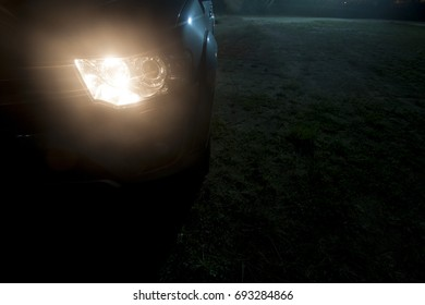 Cars parked in a grassy parking lot during the night with the headlights on.