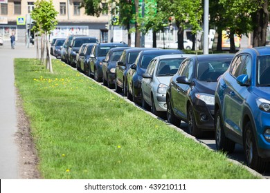 Cars parked in line on the roadside. Green grass in city street