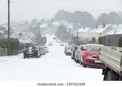Cars parked on a road in suburbia in the snow
