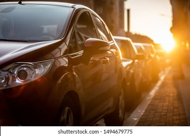 Cars parked on the side of the road, with sunset background.