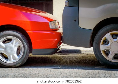 Cars are parked on the street very tightly to each other. A common way of parking in large European cities.