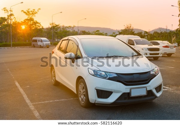 Cars parked in outdoor parking lot at a park in the evening time with  sunlight of sunset and beautiful orange sky background