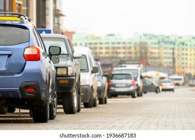 Cars parked in a row on a city street side.