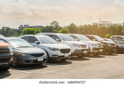 Cars parking in asphalt parking lot in a row with trees, cloudy sky background in a park. Outdoor parking lot with fresh ozone, green environment of transportation and technology concept