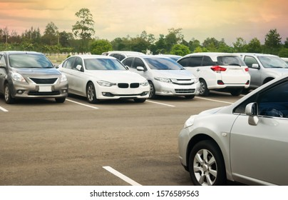 Cars parking in asphalt parking lot with trees, cloudy sky background in a park. Outdoor parking lot with fresh ozone, green environment of transportation and technology concept