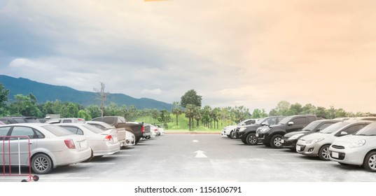 Cars parking in large asphalt parking lot in two rows with trees, sky, mountain background in a park. Outdoor parking lot with fresh ozone, green environment of transportation and technology concept