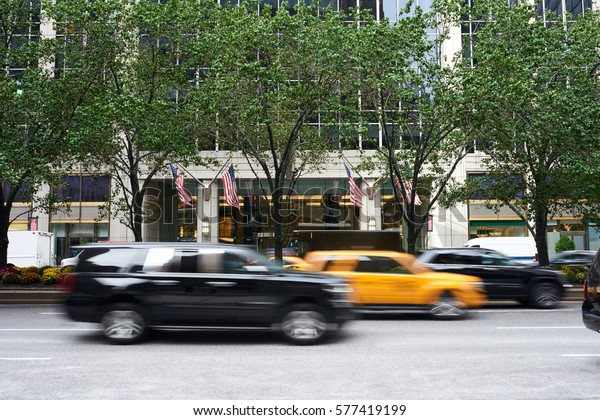 Cars passing by in motion blur busy financial street in New York