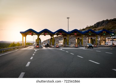 Cars passing through the toll gate on the motorway, dark journey background with sunflare