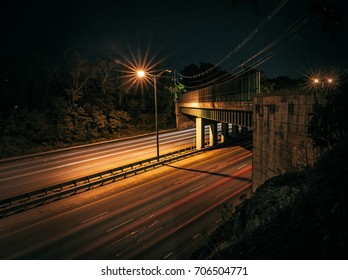 Cars passing under a bridge at night taken from up on a cliff