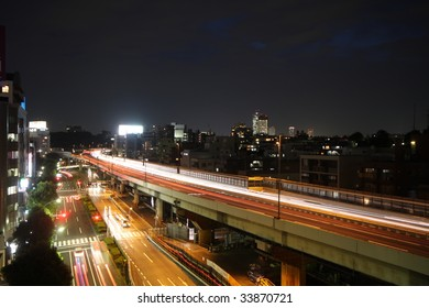 Cars racing at night on a highway and street in Tokyo, Japan