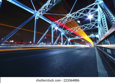 cars run fast across the highway of colorful steel bridge at night