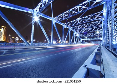 cars run fast through the colorful steel bridge with long tail at night