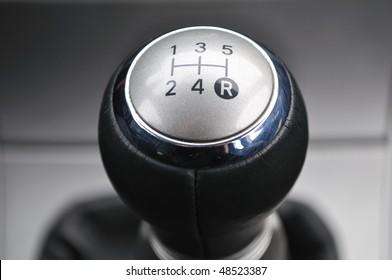 Car's shift lever. Macro shot on chrome gear stick. Gearshift.