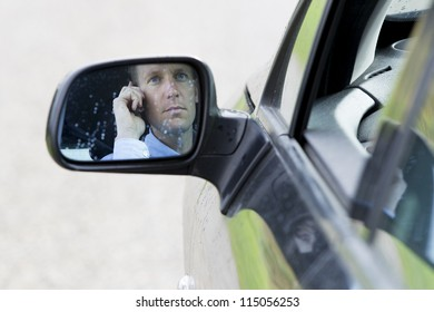 Car's side-view mirror reflecting male driver using mobile phone. Horizontal shot.