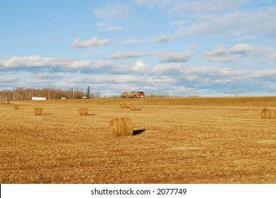cars and trucks on country side road through harvest fields