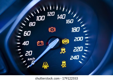 Car's, vehicle's speedometer with visible information display - ignition warning lamp  and brake system warning lamp, visible symbols of instrument cluster, with warning lamps illuminated.