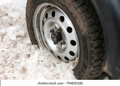 The car's wheel was stuck in the winter in the snow on the street.