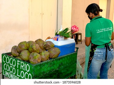 Cartagena, Bolívar, Colombia; 12-02-2020: Cart with fresh coconuts for sale in a downtown street business run by a young woman.
