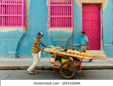 Cartagena, Colombia. April 2018. A view of a mobile fruit and vegetable seller outside a colourful building, on Calle Quero , in Cartagena, Colombia.