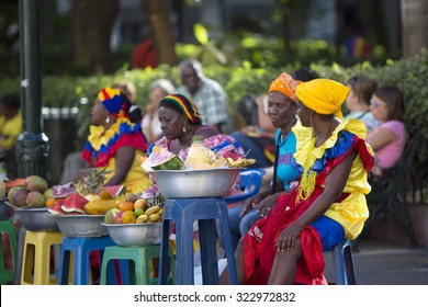 CARTAGENA, COLOMBIA, JANUARY 11: Black Colombian women sitting and selling fruits at the old colonial city of Cartagena with the traditional clothes. Colombia 2014
