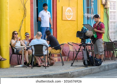 Cartagena, Colombia - January 23th, 2018: A cameraman reading a menu at the Solar Bar, colonial style in the Calle de San Antonio at Getsemani district in Cartagena, Colombia.