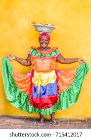 CARTAGENA, COLOMBIA - June 18, 2017: Colorful Colombian market woman sells tasty snacks from a dish carried on her head to both locals and international tourists in the streets of Cartagena, Columbia.