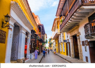 CARTAGENA, COLOMBIA - October 22, 2017: Unidentified people walking and taking pictures in Cartagena city street with colorful building of Cartagena Walled City