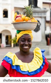 CARTAGENA, COLOMBIA - SEPTEMBER 16, 2019: Unidentified palenquera, fruit seller lady on the street of Cartagena.These Afro-Colombian women come from village San Basilio de Palenque, just outside.
