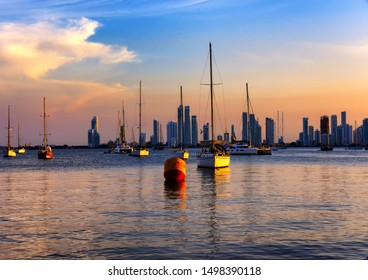 Cartagena de Indias, Bolivar/Colombia, 06/19/2019: Panoramical view of boats in Cartagena bay at the sunset with the buildings of Castillo Grande in the background.