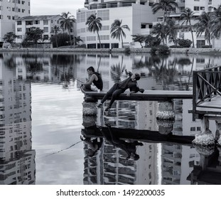 "Cartagena de Indias, Bolivar/Colombia, 08/07/2019: Two friends in the little lake called ""El Laguito"", one fishing and the other taking photo of the activity with his cellphone"