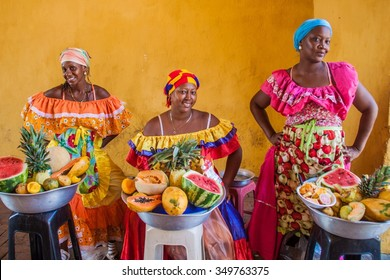 CARTAGENA DE INDIAS, COLOMBIA - AUG 28, 2015: Women wearing traditional costume sell fruits in the center of Cartagena.