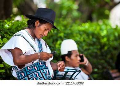 CARTAGENA DE INDIAS, COLOMBIA - AUGUST, 2018: Two Arhuaco men dressed with their traditional clothes using their cellphones in Cartagena de Indias