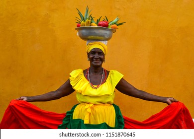 CARTAGENA DE INDIAS, COLOMBIA - July 27, 2017: Beautiful smiling woman wearing traditional costume sell fruits in the center of Cartagena.