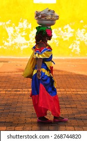 CARTAGENA DE INDIAS, COLOMBIA - JUNE 15, 2014: Colombian woman in Cartagena de Indias with the traditional dress. In Colombia is usual to transport fresh fruit and food on the head.