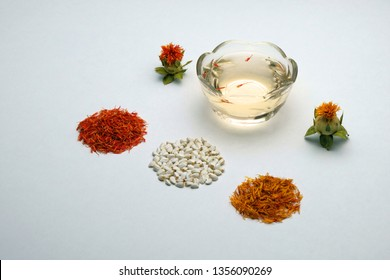 Carthamus tinctorius eco-friendly safflower. Flowering and saffron flowers. Seeds for home garden. Spices and cosmetic oil from safflower on a white background. Copy space.