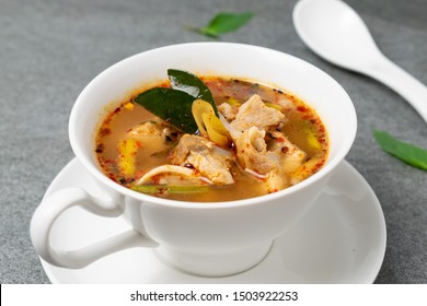 Cartilage pork stewed in spicy soup with Thai spices in white bowl on concrete table.