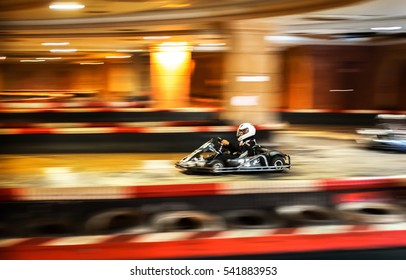 Carting competitions. Driver in helmet on kart circuit