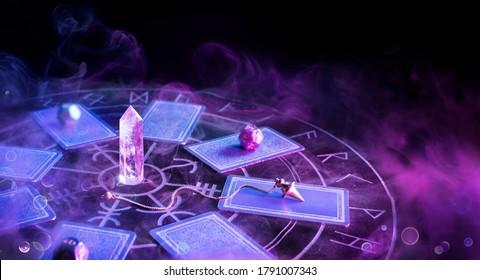 Cartomancy - Pendulum On Blurred Altar With Defocused Tarot Cards