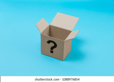 carton box with question mark character on pastel blue background. colorful paper backdrop with copy space. brown box isolated on modern blue.